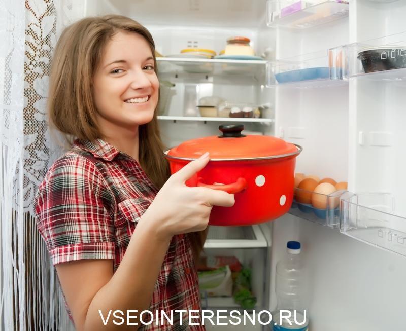 teenager-girl-putting-pan-into-fridge-at-home