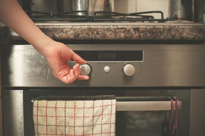 the-hand-of-a-young-woman-is-turning-the-knob-on-a-stove
