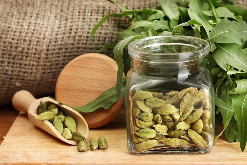 jar-of-green-cardamom-with-rocket-on-canvas-background-close-up