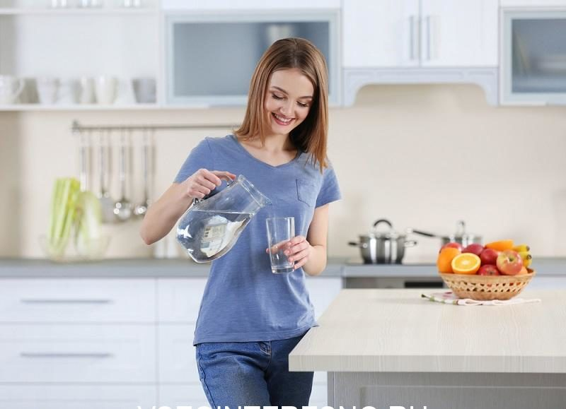 young-woman-pouring-water-from-jug-into-glass-in-the-kitchen-2