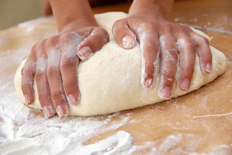 female-hands-in-flour-closeup-kneading-dough-on-table