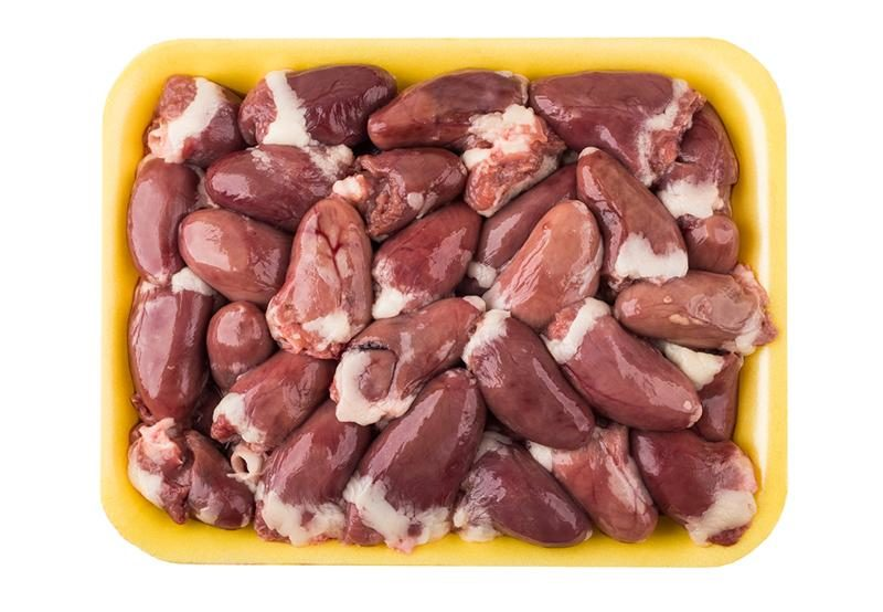 raw-chicken-hearts-in-yellow-plastic-tray-isolated-on-white