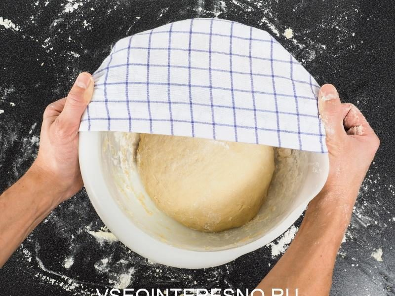 person-covering-a-dough-for-proving-in-a-bowl-on-black-table
