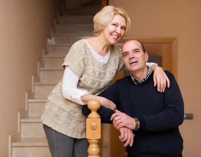 smiling-spouses-leaning-against-stairway