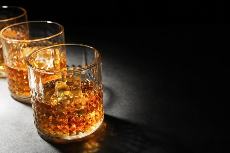glasses-of-whisky-on-grey-textured-table-closeup