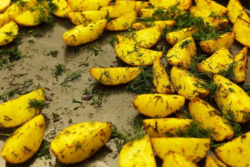 golden-baked-potato-with-dill-on-a-metal-baking-sheet