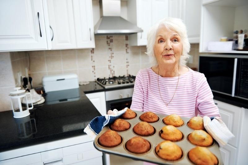 a-grandmother-holding-a-tray-of-muffins-in-the-kitchen