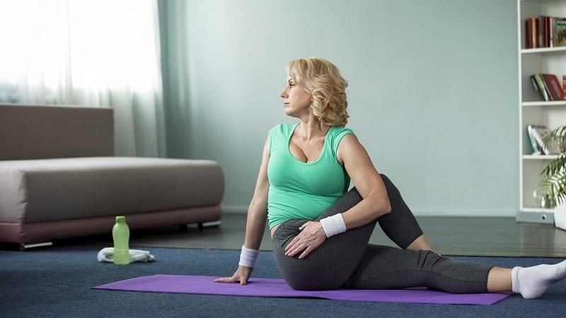beautiful-mature-female-practicing-twisting-sage-pose-at-home-yoga-time-sport