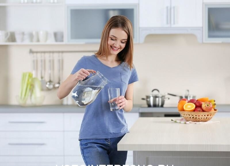 young-woman-pouring-water-from-jug-into-glass-in-the-kitchen