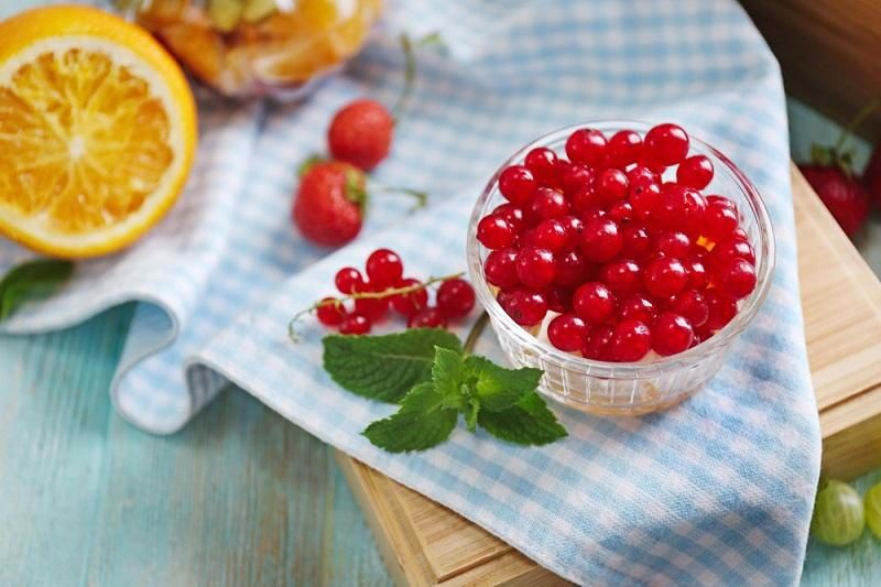 fresh-red-currant-and-orange-in-glass-bowl-on-wooden-box