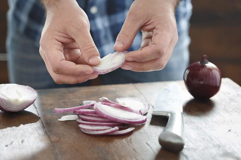 male-hands-chopped-fresh-red-onion-wooden-table